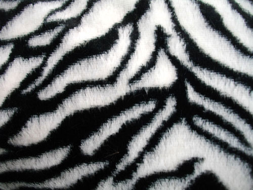 The sleek lines of this collarless duster coat, combined with the sophisticated beauty of the softly muted zebra pattern and the luxe feel of the faux fur, ensure that this is a .
